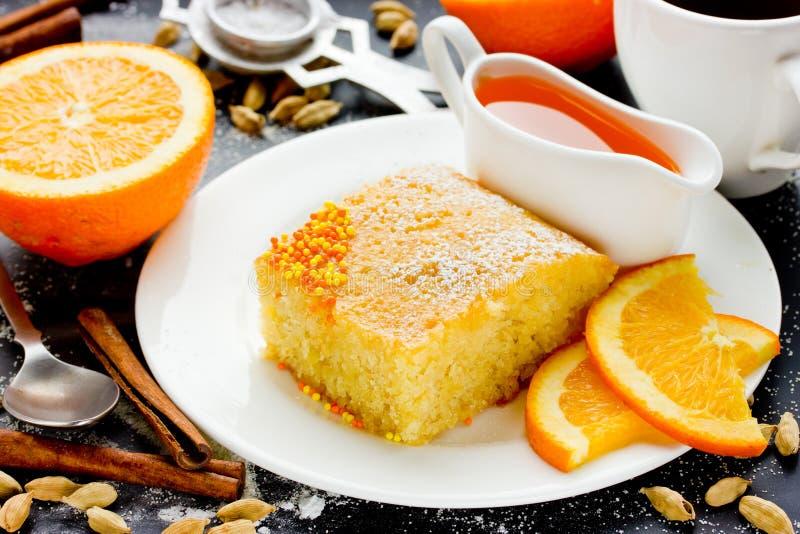 Γλυκιά πίτα Basbousa (Namoora) με το πορτοκαλί semoli καρύδων καρδάμωμων στοκ εικόνα