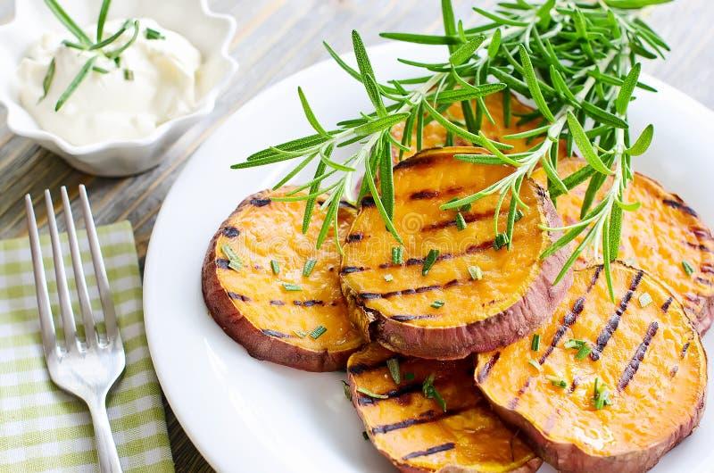 Γλυκιά πατάτα που ψήνεται και που ψήνεται στη σχάρα με τη σάλτσα δεντρολιβάνου ANS στοκ εικόνες