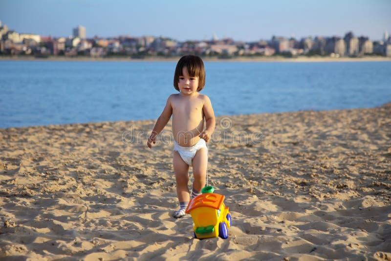 Γλυκό λίγο μωρό που παίζει με το φωτεινό παιχνίδι άμμου στην παραλία στοκ εικόνα με δικαίωμα ελεύθερης χρήσης
