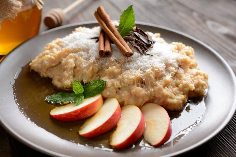 Γλυκό κουάκερ κεχριού με το μέλι, τα μήλα και την ξυμένη καρύδα στοκ φωτογραφίες