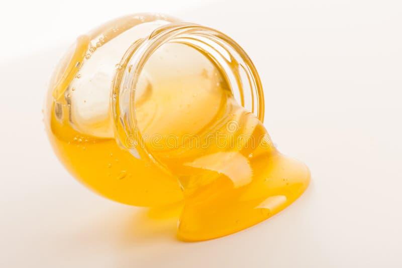 Γλυκό κολλώδες χρυσό μέλι που ρέει έξω του βάζου γυαλιού στοκ φωτογραφίες