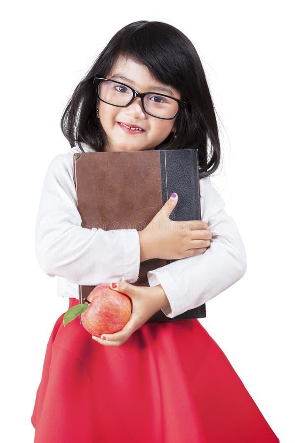 Γλυκό μικρό κορίτσι με το βιβλίο και το μήλο στοκ φωτογραφία