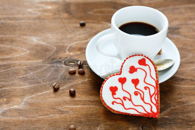 Γλυκό μπισκότο για την ημέρα του βαλεντίνου με τον καφέ στο κοντραπλακέ στοκ φωτογραφίες