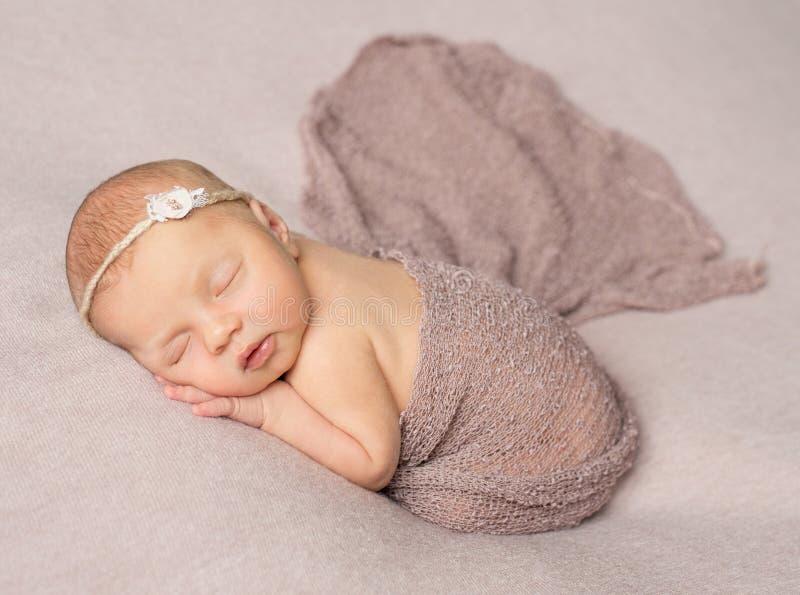 Γλυκό νεογέννητο κορίτσι ύπνου που καλύπτεται με το σάλι στοκ εικόνα