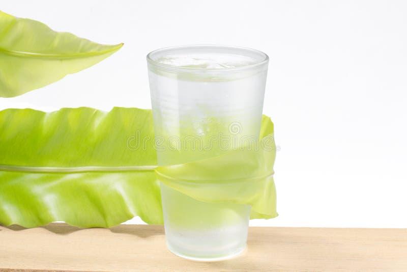 Γλυκό νερό στο γυαλί με το πράσινο φύλλο στο λευκό στοκ φωτογραφία με δικαίωμα ελεύθερης χρήσης