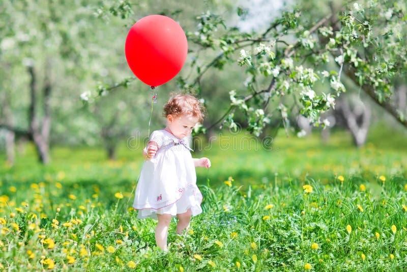Γλυκό παιχνίδι κοριτσάκι με ένα μεγάλο κόκκινο μπαλόνι στοκ εικόνα