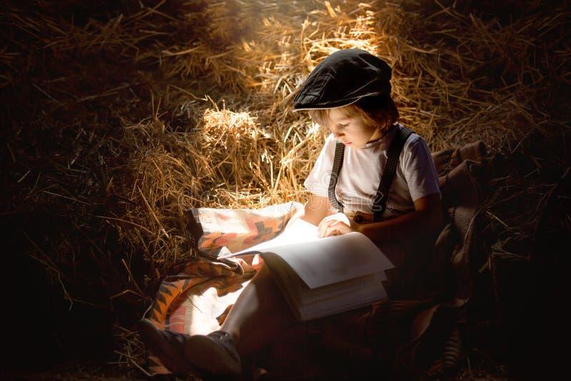 Γλυκό παιδί, αγόρι, που διαβάζει ένα βιβλίο στη σοφίτα σε ένα σπίτι, sittin στοκ φωτογραφίες