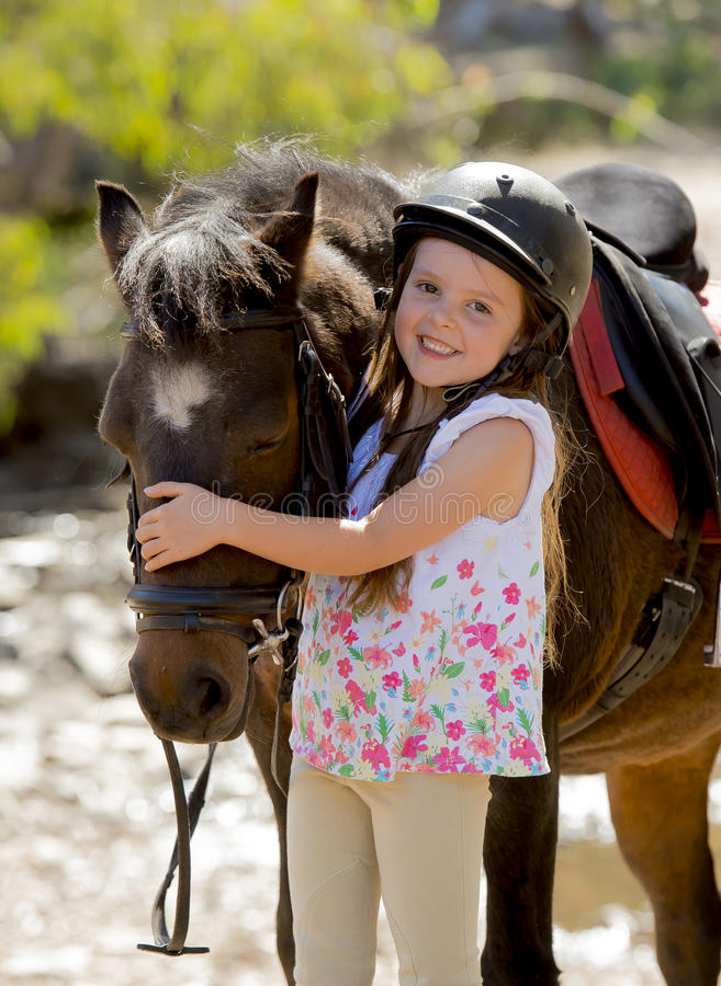 Γλυκό όμορφο νέο κορίτσι 7 ή 8 χρονών που αγκαλιάζει το κεφάλι λίγου αλόγου πόνι που χαμογελά το ευτυχές φορώντας jockey ασφάλεια στοκ φωτογραφία με δικαίωμα ελεύθερης χρήσης