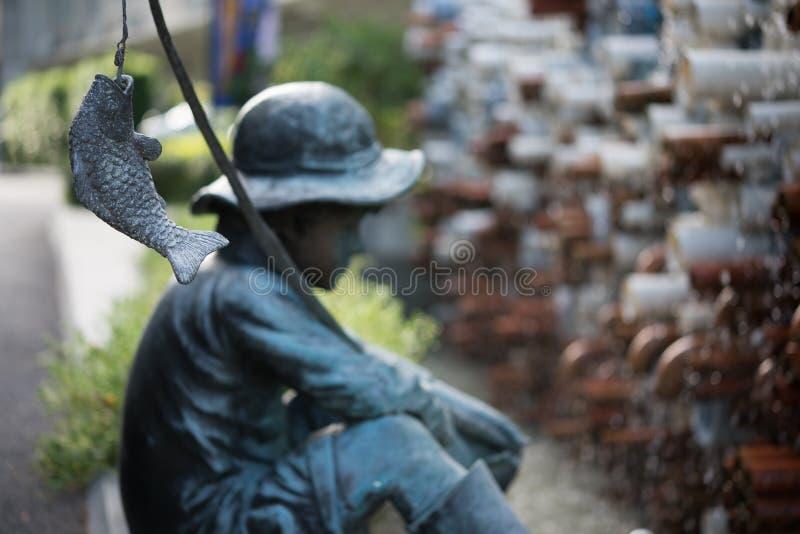 Γλυπτό του μικρού παιδιού που αλιεύει στον κήπο στοκ φωτογραφίες