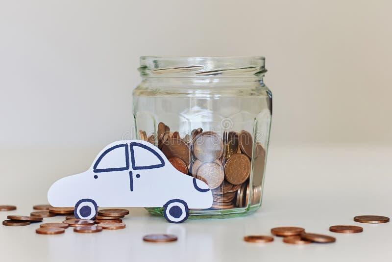 Δάνειο αυτοκινήτων, έννοια ασφαλείας αυτοκινήτου Σύνολο βάζων γυαλιού των νομισμάτων και του αυτοκινήτου της Λευκής Βίβλου στοκ φωτογραφία