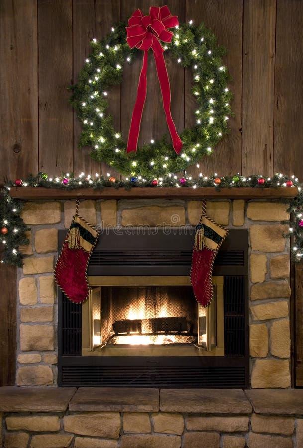 Δάπεδο τζακιού εστιών Χριστουγέννων με το στεφάνι και τις γυναικείες κάλτσες