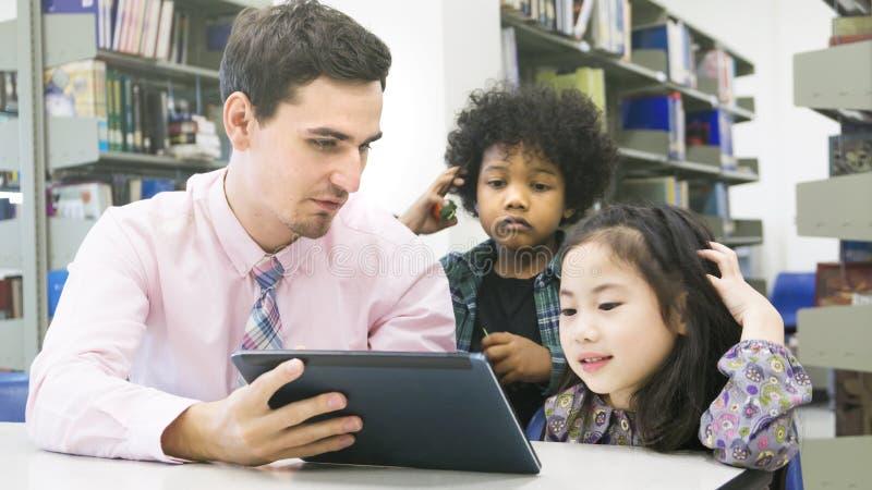 Δάσκαλος ατόμων και σπουδαστές παιδιών που μαθαίνουν και που κοιτάζουν στο devi ταμπλετών στοκ φωτογραφία με δικαίωμα ελεύθερης χρήσης