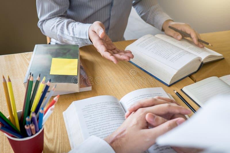 Δάσκαλος, εκμάθηση, εκπαίδευση, ομάδα εφήβου που μαθαίνει μελετώντας το νέο μάθημα στη γνώση στη βιβλιοθήκη κατά τη διάρκεια της  στοκ εικόνες
