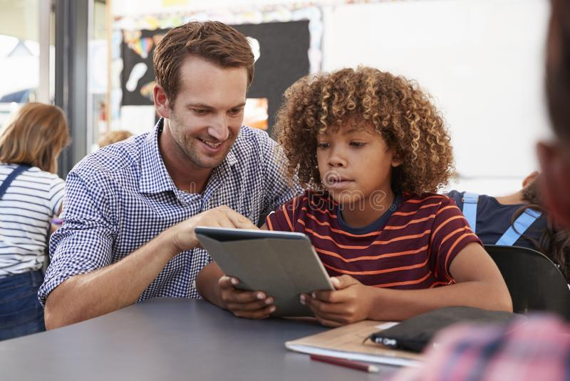 Δάσκαλος και μαθητής που χρησιμοποιούν τον υπολογιστή ταμπλετών στην κατηγορία στοκ φωτογραφία