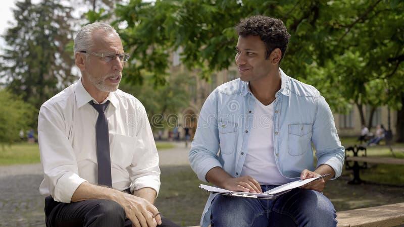 Δάσκαλος λογοτεχνίας που δίνει τις συμβουλές στον ισπανικό σπουδαστή για το γράψιμο δοκίμιου στοκ εικόνα