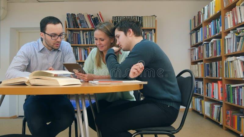 Δάσκαλος με την ομάδα σπουδαστών που εργάζονται στην ψηφιακή ταμπλέτα στη βιβλιοθήκη στοκ εικόνες με δικαίωμα ελεύθερης χρήσης