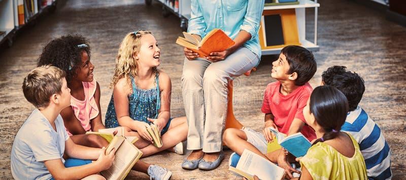 Δάσκαλος με τους σπουδαστές που διαβάζουν τα βιβλία στοκ φωτογραφία