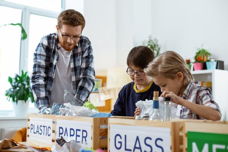 Δάσκαλος πιπεροριζών στα σαφή γυαλιά που εξηγεί τις βάσεις ανακύκλωσης στοκ φωτογραφίες