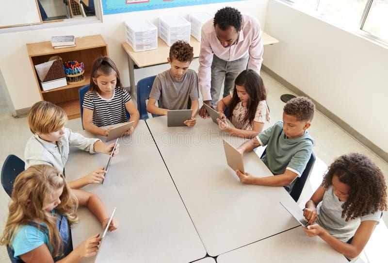 Δάσκαλος που βοηθά τα παιδιά που χρησιμοποιούν τις ταμπλέτες στο μάθημα, ανυψωμένη άποψη στοκ φωτογραφίες με δικαίωμα ελεύθερης χρήσης
