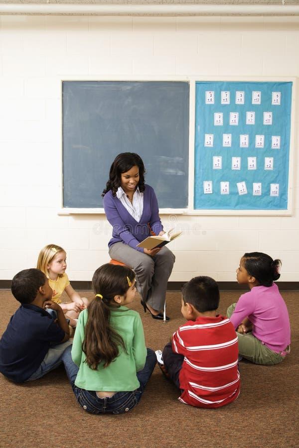 Δάσκαλος που διαβάζει στους σπουδαστές στοκ φωτογραφία με δικαίωμα ελεύθερης χρήσης