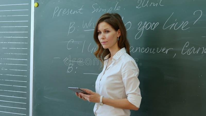 Δάσκαλος που μιλά με την κατηγορία κοντά στον πίνακα στοκ φωτογραφίες με δικαίωμα ελεύθερης χρήσης