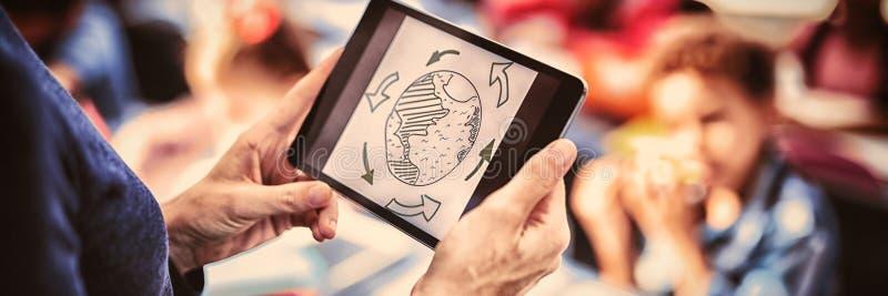 Δάσκαλος που χρησιμοποιεί την ψηφιακή ταμπλέτα διδάσκοντας στην τάξη στοκ εικόνα με δικαίωμα ελεύθερης χρήσης