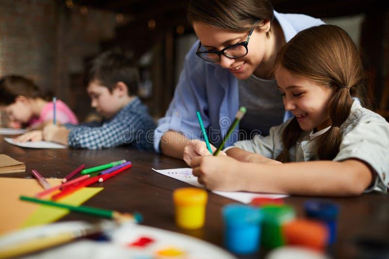 Δάσκαλος τέχνης που συνεργάζεται με τα παιδιά στοκ εικόνα με δικαίωμα ελεύθερης χρήσης