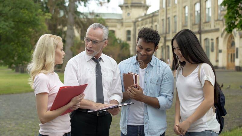 Δάσκαλος φυσικής που συζητά τη επιστημονική έρευνα με την ομάδα σπουδαστών, ομαδική εργασία στοκ εικόνες
