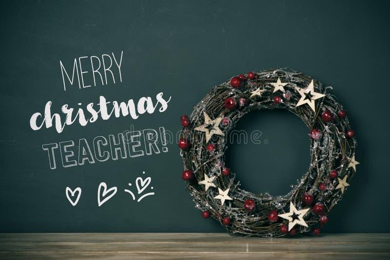 Δάσκαλος Χαρούμενα Χριστούγεννας στεφανιών και κειμένων στοκ εικόνες