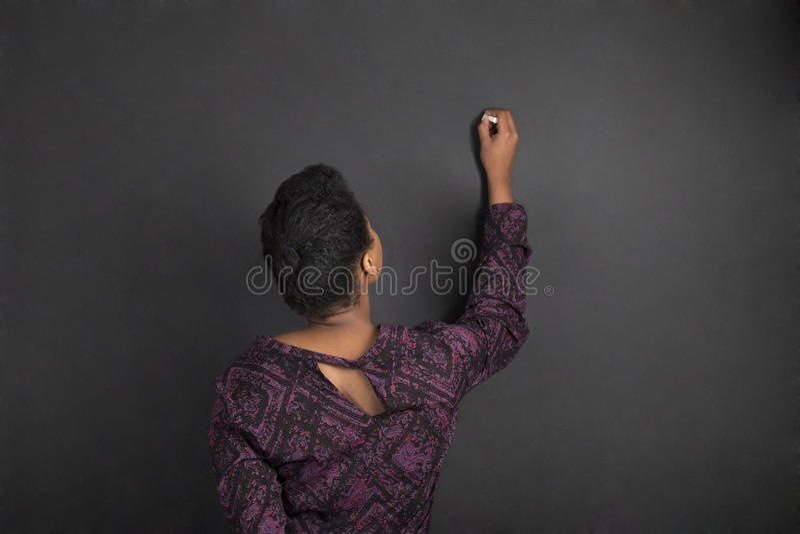 Δάσκαλος γυναικών αφροαμερικάνων που γράφει στο μαύρο υπόβαθρο πινάκων κιμωλίας στοκ φωτογραφία