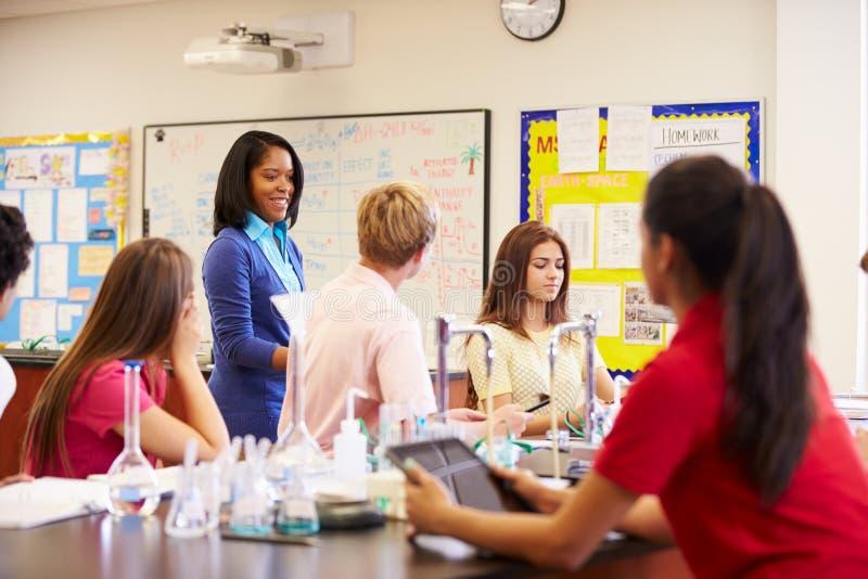 Δάσκαλος και μαθητές στην κατηγορία επιστήμης γυμνασίου στοκ εικόνα