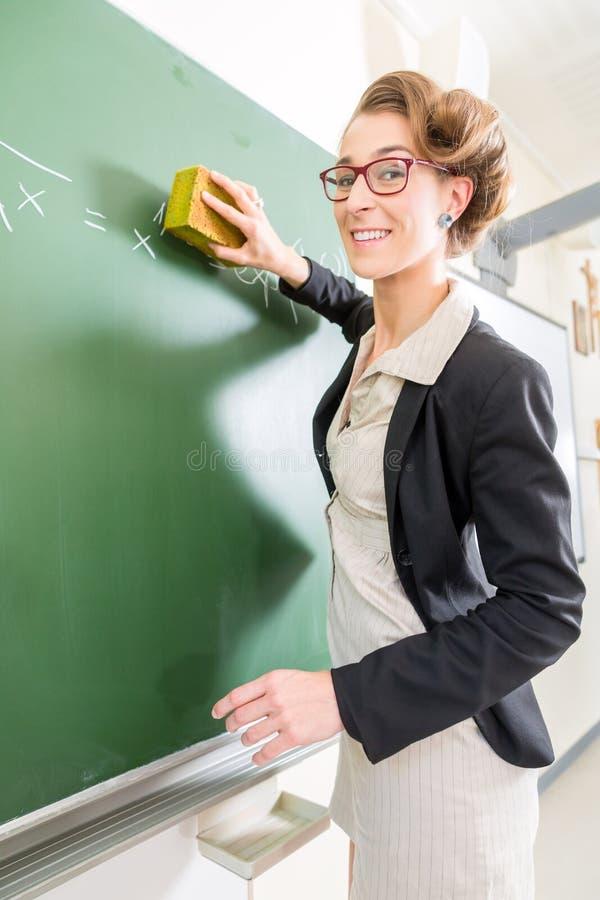 Δάσκαλος με ένα σφουγγάρι μπροστά από μια σχολική τάξη στοκ φωτογραφίες με δικαίωμα ελεύθερης χρήσης