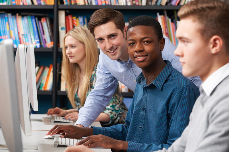 Δάσκαλος με την ομάδα εφηβικών σπουδαστών που χρησιμοποιούν τους υπολογιστές στοκ εικόνα με δικαίωμα ελεύθερης χρήσης