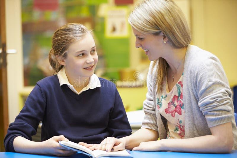 Δάσκαλος με τη θηλυκή ανάγνωση μαθητών στο γραφείο στην τάξη στοκ εικόνες