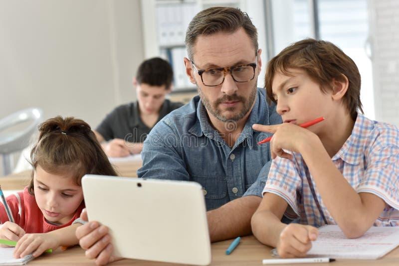 Δάσκαλος με τους σπουδαστές στην κατηγορία που χρησιμοποιεί την ταμπλέτα στοκ φωτογραφία με δικαίωμα ελεύθερης χρήσης