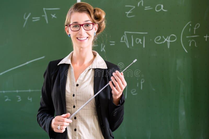 Δάσκαλος με το δείκτη μπροστά από μια σχολική τάξη στοκ εικόνες