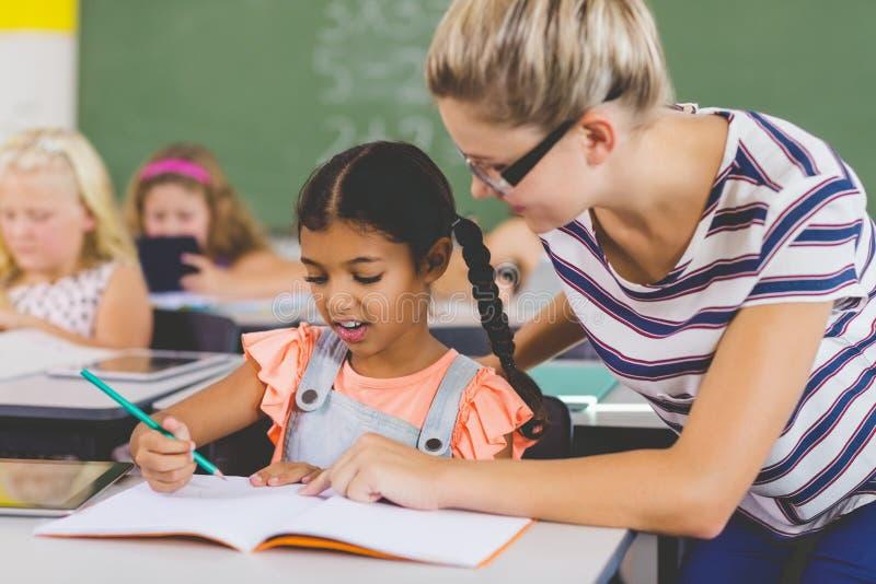 Δάσκαλος που βοηθά τα παιδιά με την εργασία τους στην τάξη στοκ εικόνα με δικαίωμα ελεύθερης χρήσης