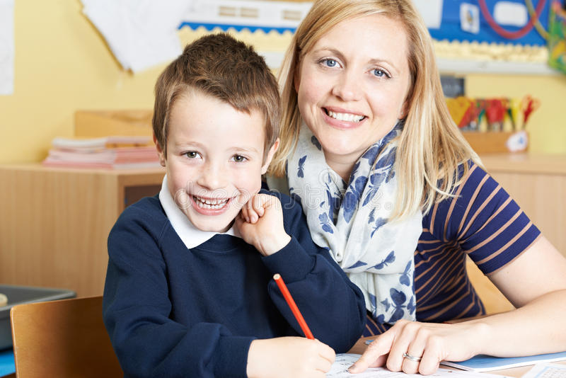 Δάσκαλος που βοηθά την αρσενική στοιχειώδη εργασία μαθητών στο γραφείο στοκ φωτογραφία με δικαίωμα ελεύθερης χρήσης