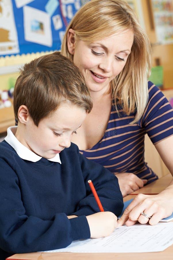 Δάσκαλος που βοηθά την αρσενική στοιχειώδη εργασία μαθητών στο γραφείο στοκ φωτογραφία