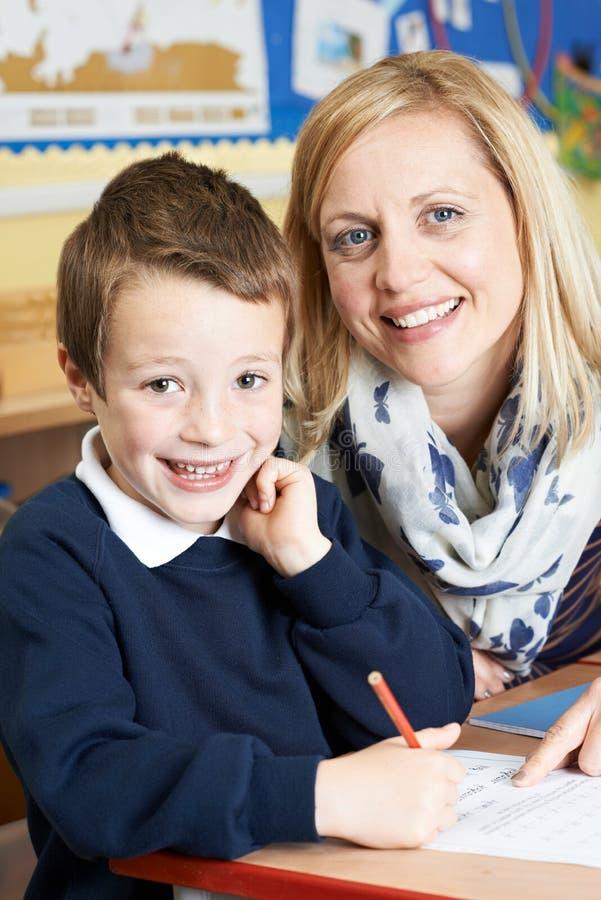 Δάσκαλος που βοηθά την αρσενική στοιχειώδη εργασία μαθητών στο γραφείο στοκ εικόνες