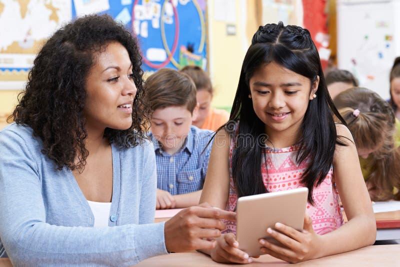 Δάσκαλος που βοηθά την ομάδα στοιχειωδών παιδιών σχολείου στον υπολογιστή στοκ φωτογραφίες