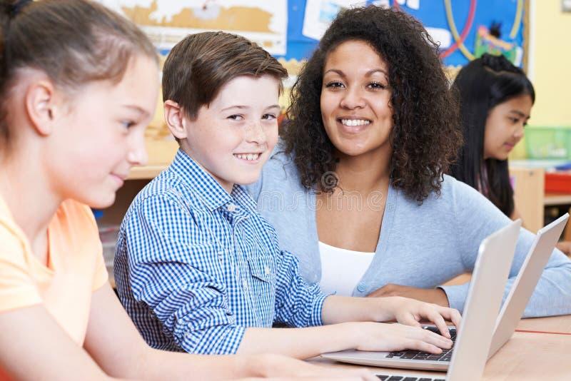 Δάσκαλος που βοηθά την ομάδα στοιχειωδών παιδιών σχολείου στον υπολογιστή στοκ εικόνες