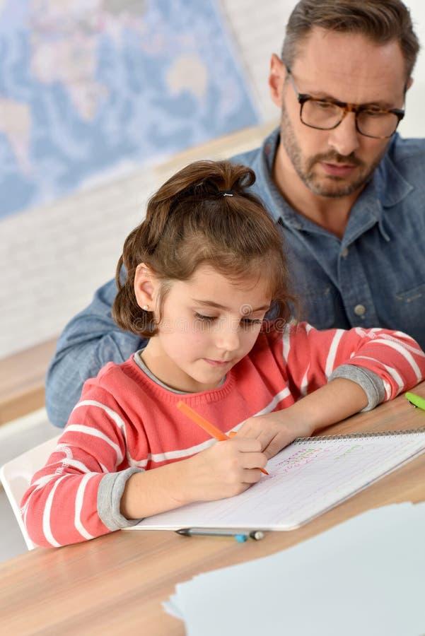 Δάσκαλος που βοηθά τη νέα μαθήτρια στην κατηγορία στοκ εικόνες