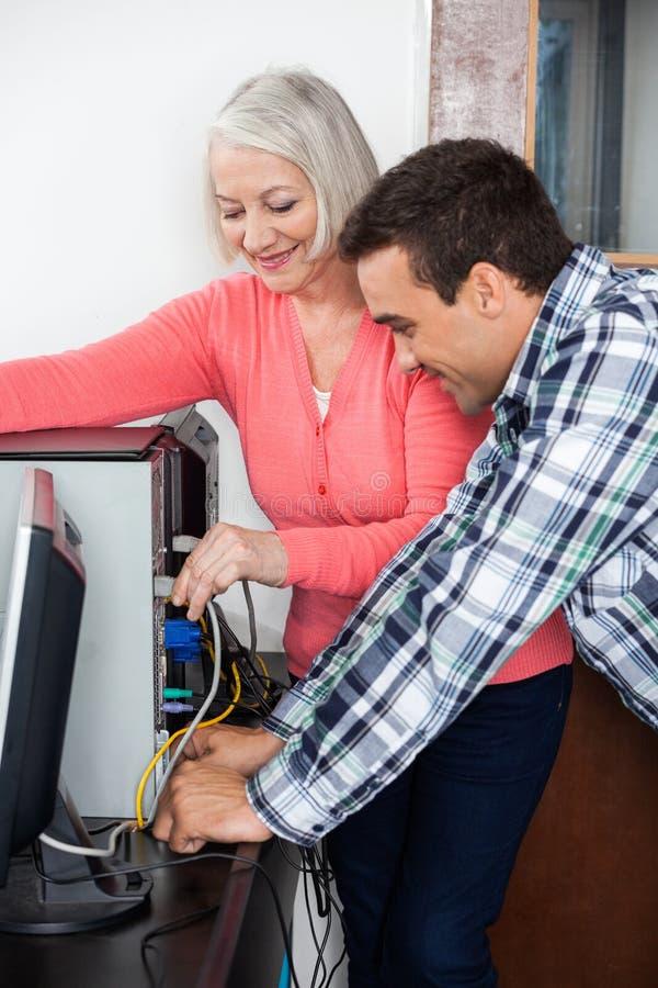 Δάσκαλος που βοηθά τον ανώτερο υπολογιστή καθιέρωσης σπουδαστών στοκ φωτογραφία
