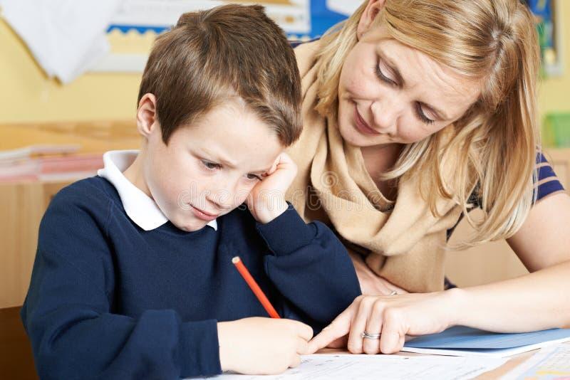 Δάσκαλος που βοηθά τον αρσενικό μαθητή δημοτικού σχολείου με το πρόβλημα στοκ εικόνα με δικαίωμα ελεύθερης χρήσης