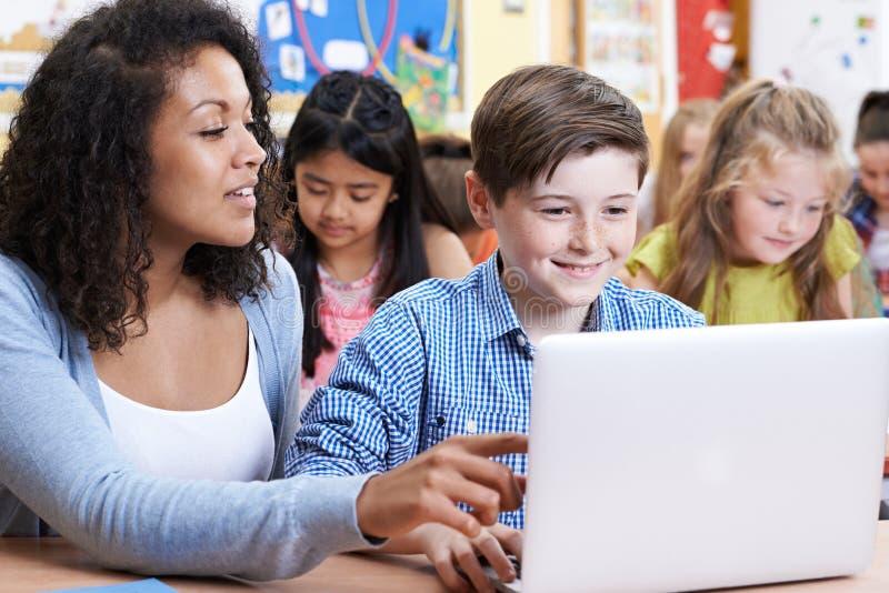 Δάσκαλος που βοηθά τον αρσενικό στοιχειώδη μαθητή στην κατηγορία υπολογιστών στοκ εικόνες