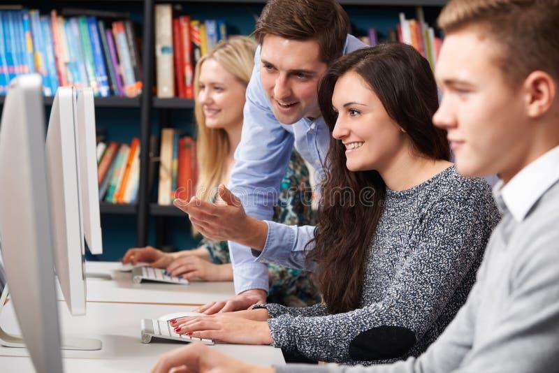 Δάσκαλος που βοηθά τους εφηβικούς σπουδαστές που εργάζονται στους υπολογιστές στοκ φωτογραφία