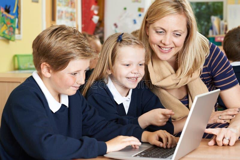 Δάσκαλος που βοηθά τους μαθητές δημοτικού σχολείου στην κατηγορία υπολογιστών στοκ φωτογραφία με δικαίωμα ελεύθερης χρήσης