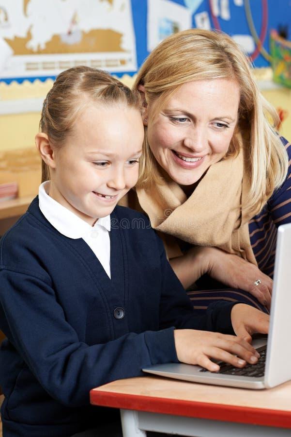 Δάσκαλος που βοηθά το θηλυκό μαθητή δημοτικού σχολείου στην κατηγορία υπολογιστών στοκ εικόνες με δικαίωμα ελεύθερης χρήσης