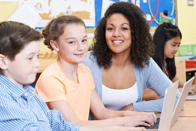 Δάσκαλος που βοηθά το θηλυκό στοιχειώδη μαθητή στην κατηγορία υπολογιστών στοκ φωτογραφίες